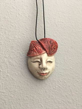 Mask necklace, porcelain/leather, $75